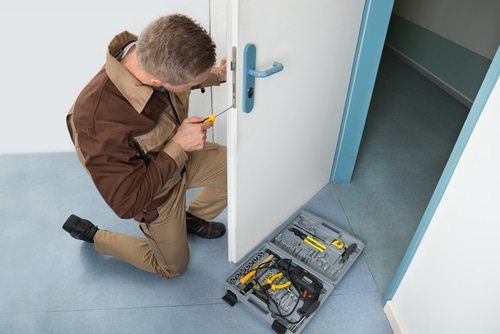A handyman fixing basic residential door handle lock